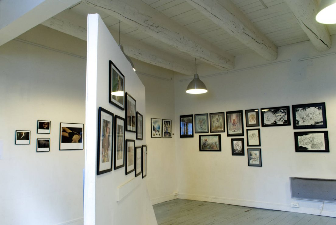 Side view of the art show featuring photographs by Agathe Mirafiore, paintings by messalyn and François Amoretti, and photographs modelled by Nella Fragola