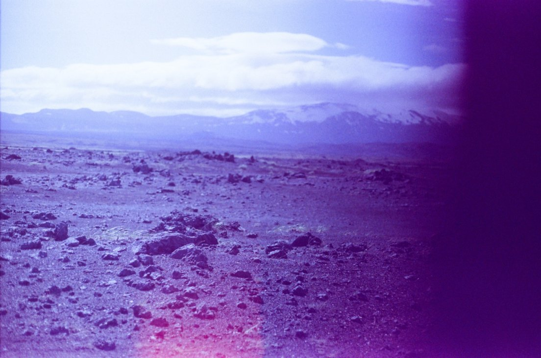 Purple-tinted photograph of the ash and lava desert in front of the volcano