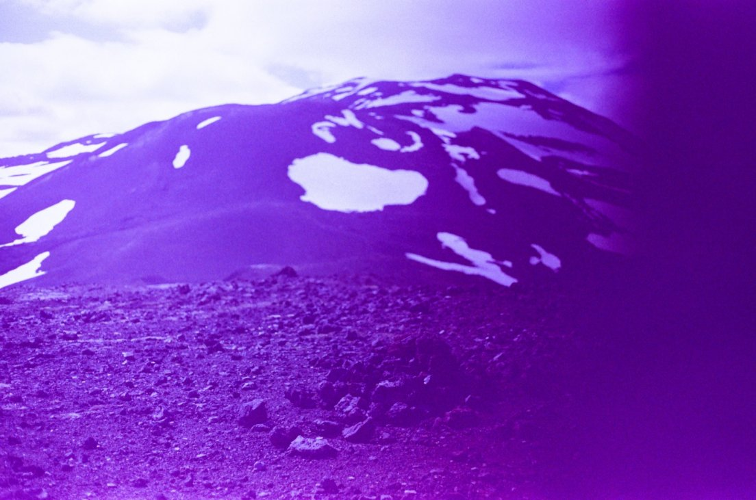 Purple-tinted photograph of the summit of the volcano with patches of snow, Hekla volcano