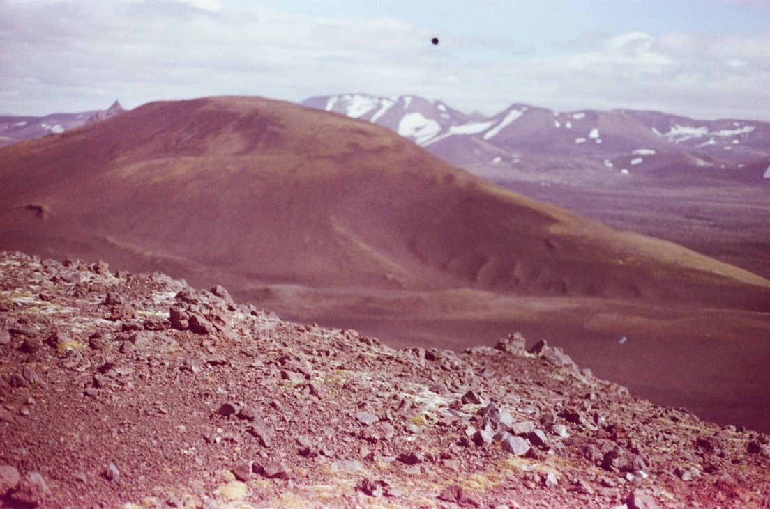 Magenta-tinted photograph of the surroundings of the volcano with lava rocks and snowy-capped mountains