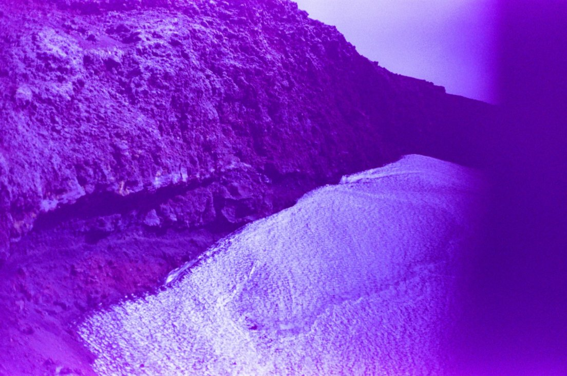 Purple-tinted photograph of a snow patch in a crater