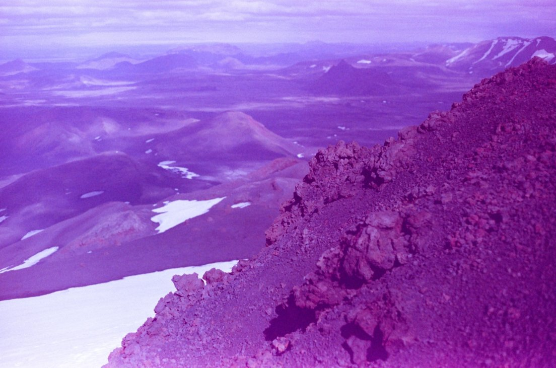 Purple-tinted photograph from the summit of the volcano of the area with patches of snow in the background