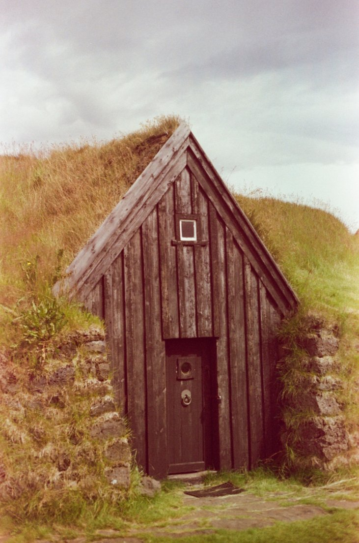 Slightly magenta-tinted photograph of a traditional icelandic farmhouse with moss-covered rooftop, Keldur