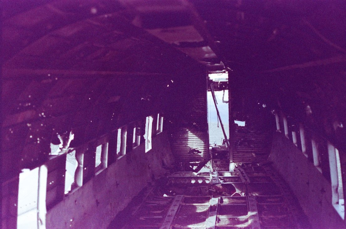 Purple-tinted photograph of the inside of the 1973 crashed plane on the black beach