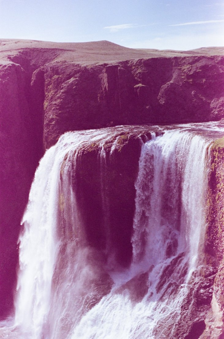 Magenta-tinted photograph of the waterfall