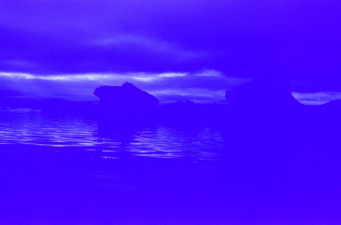 Heavily blue-tinted photograph of icebergs