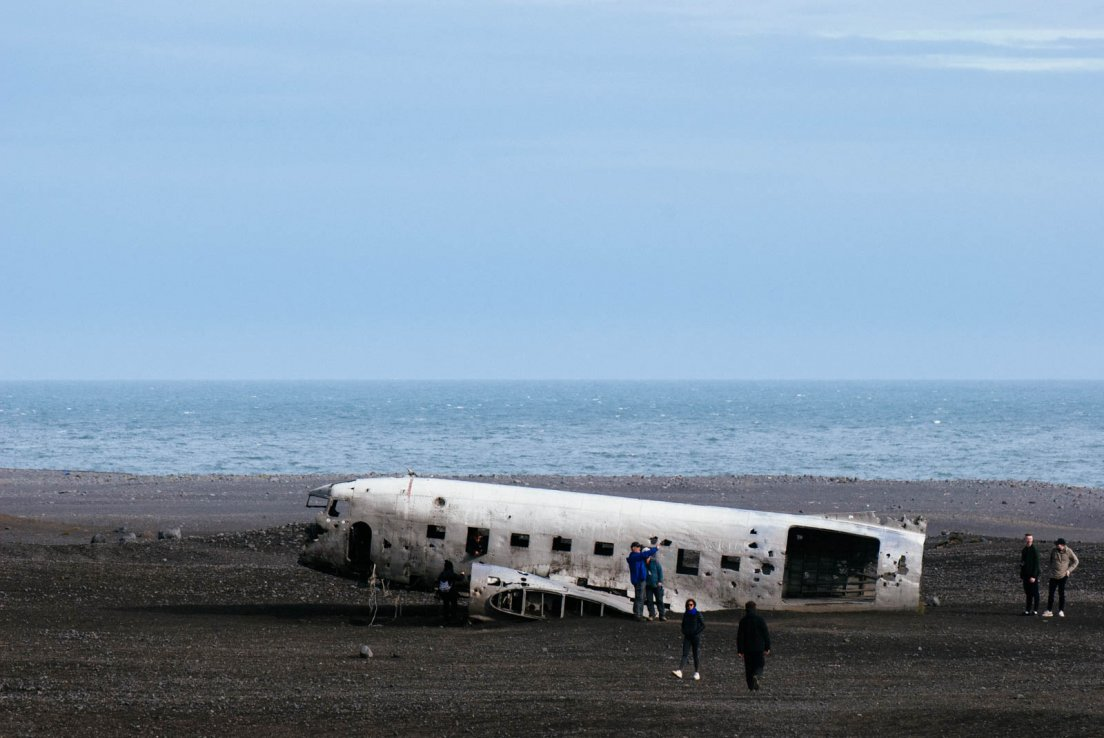 Crashed plane with a lot of missing parts by the sea