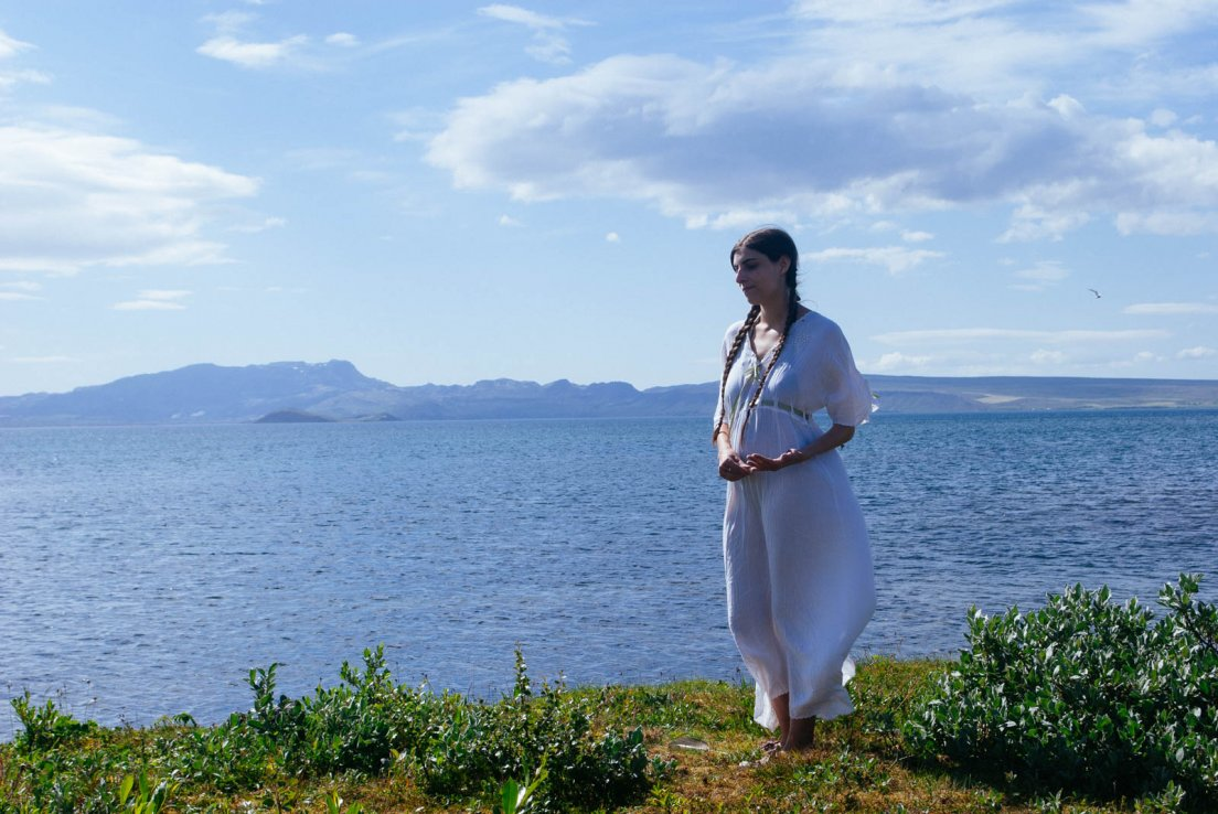 In the white Voriagh 'Louisa' dress by the shores of a lake, likely Þingvallavatn