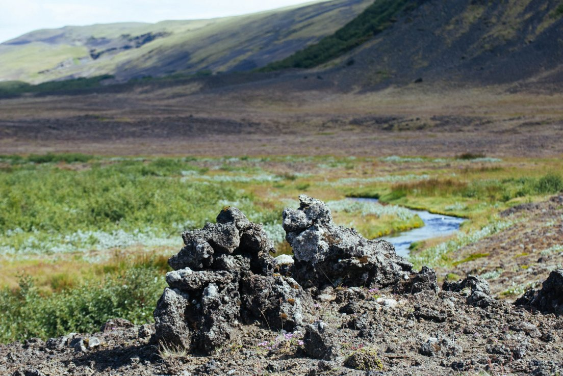 Lava rocks standing out in front of a stream crossing a valley