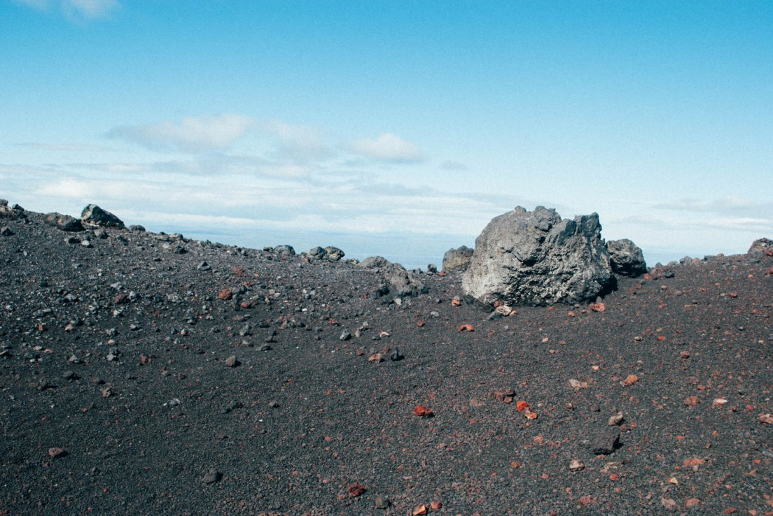 Ashes and lava rocks standing out in front of a very blue sky