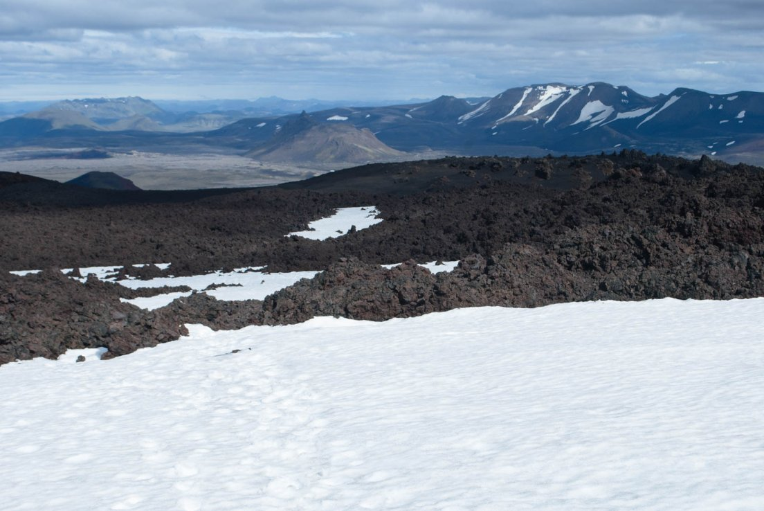 Snow, lava field and snow-capped moutains on a sunny day
