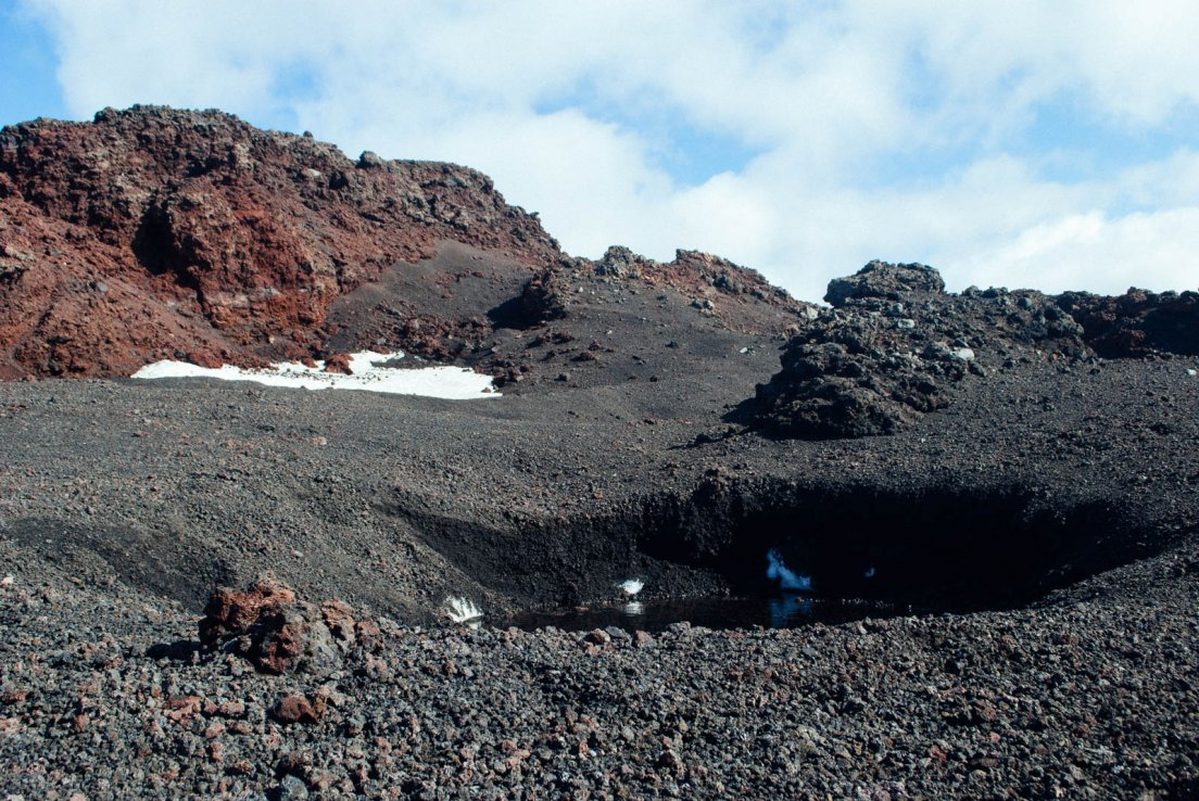 Snow patch at the black and red summit of the volcano on a sunny day