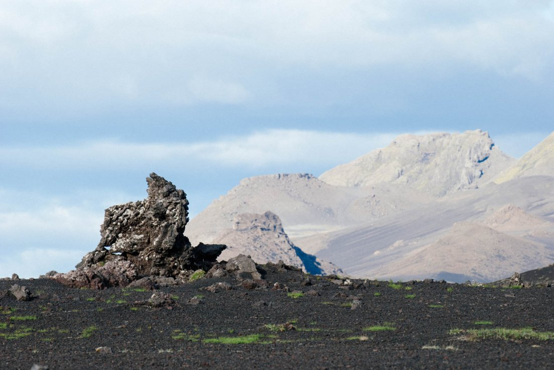 Big lava rock standing out in a ash desert on a sunny but cloudy day