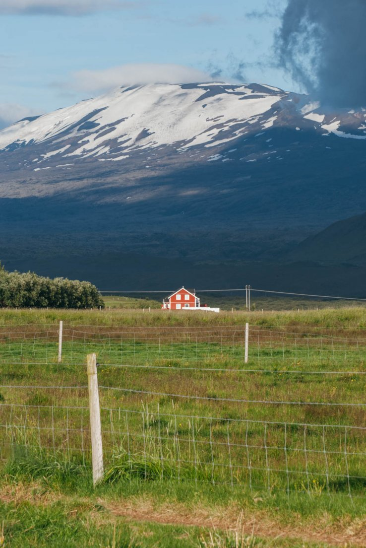 Red and white house at the center of a large meadow with Hekla in the background