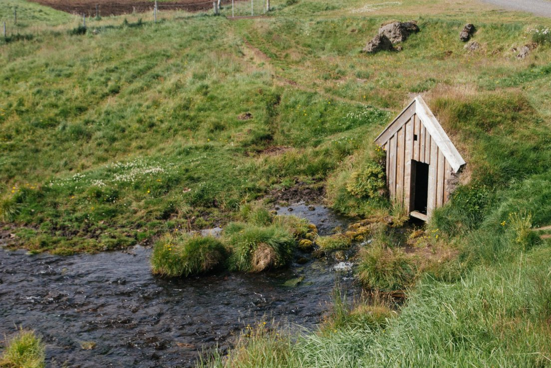 Tiny cabin next to a river with a grass rooftop