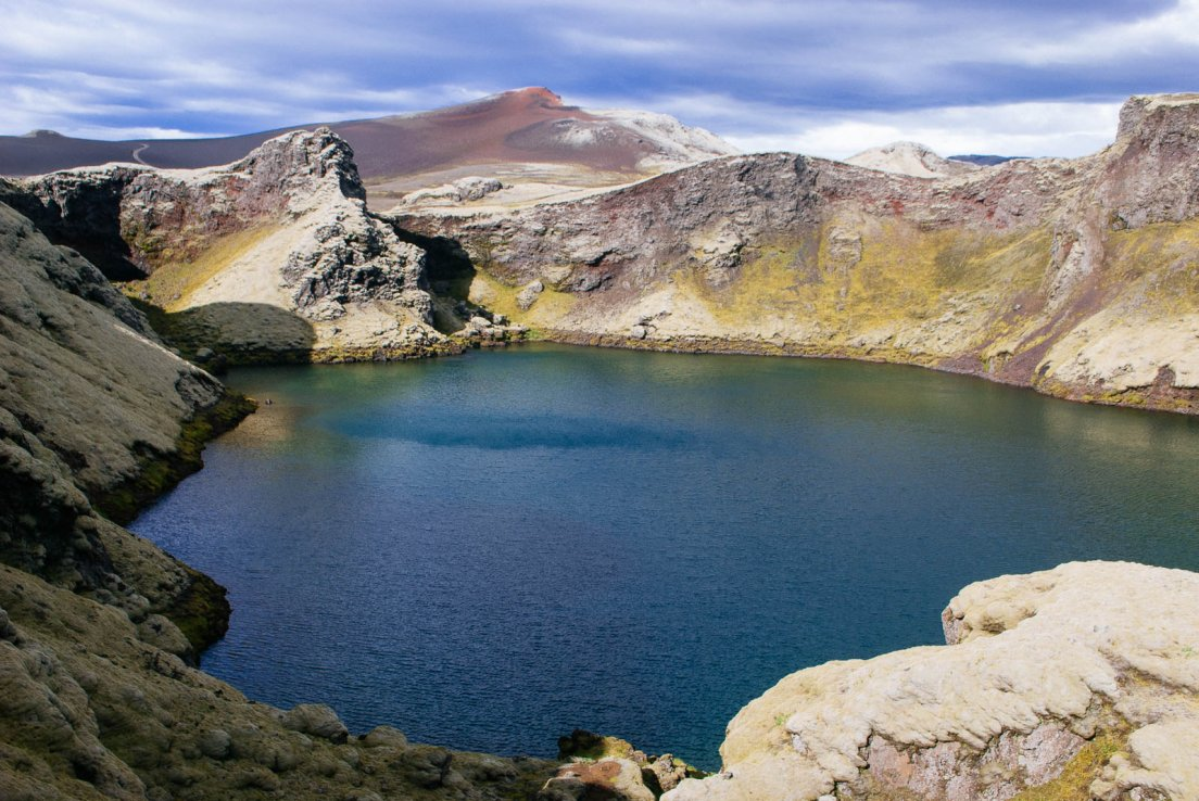 Former crater turned lake circled by rocks of many colors under a menacing sky