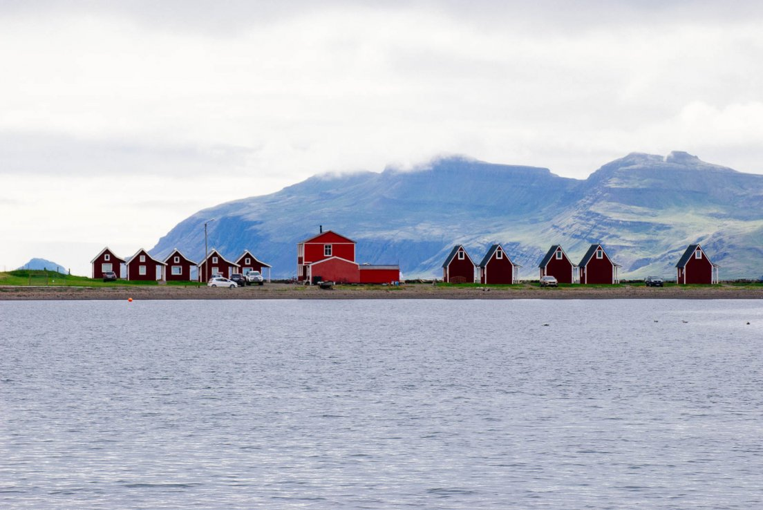 Range of small red wooden cabins by the sea with mountains in the background in the town of Eskifjörður