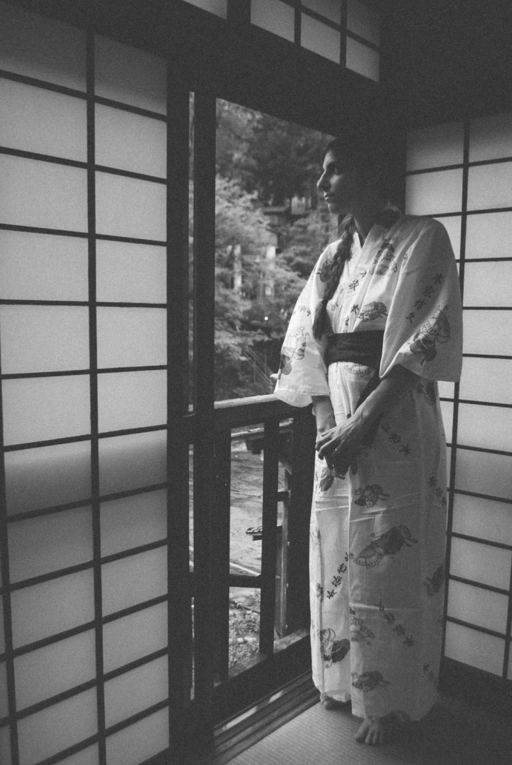 A western girl in a yukata watching over a traditional japanese window