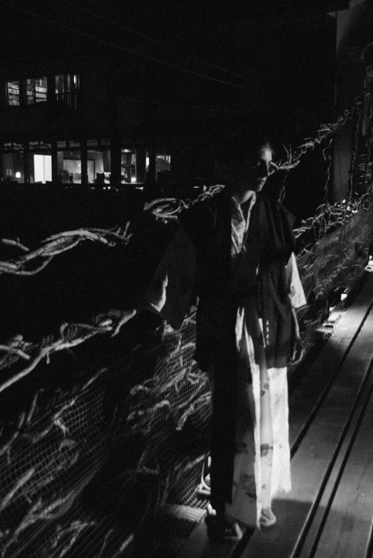 A western girl in a yukata on a suspended bridge by night