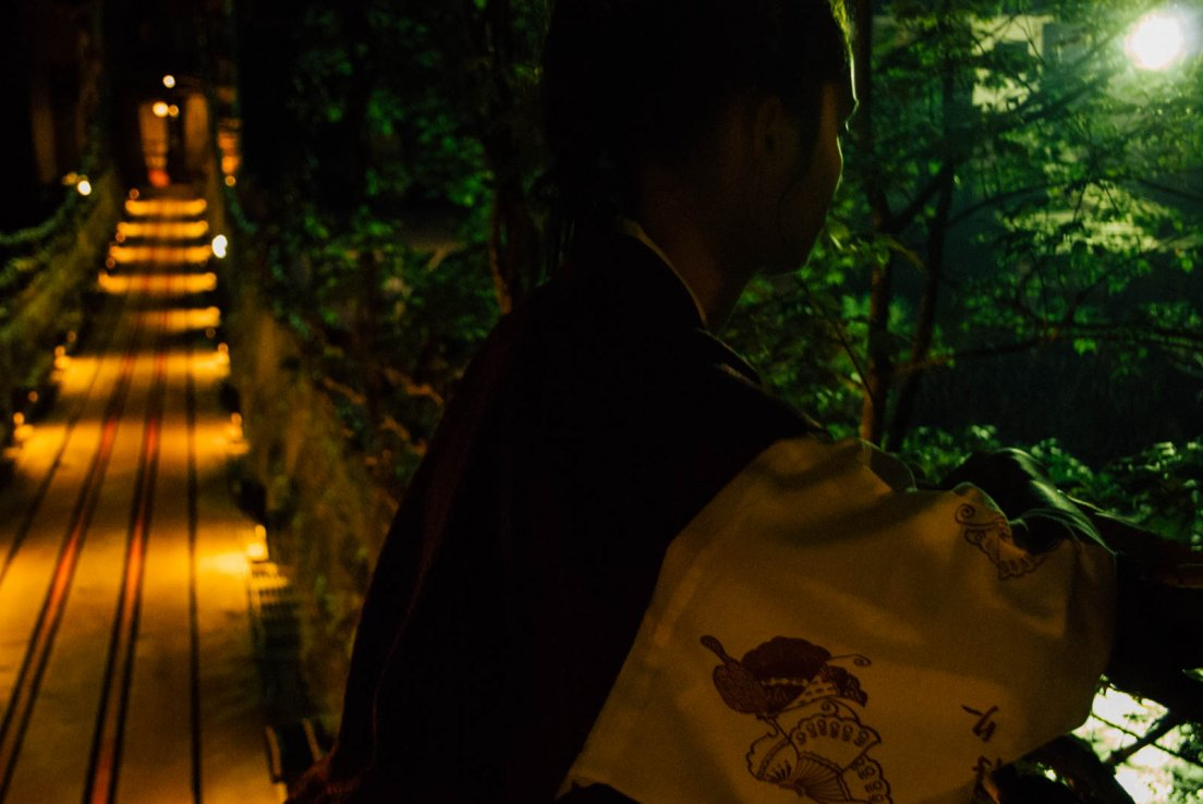 Backlit western girl in a yukata watching over a river bridge by night