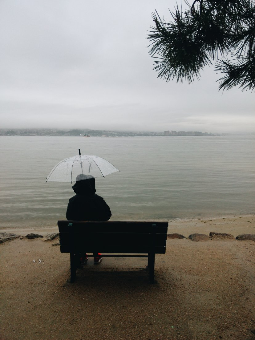 A woman sat on a bench in front of the sea with a transparent umbrella on a rainy day