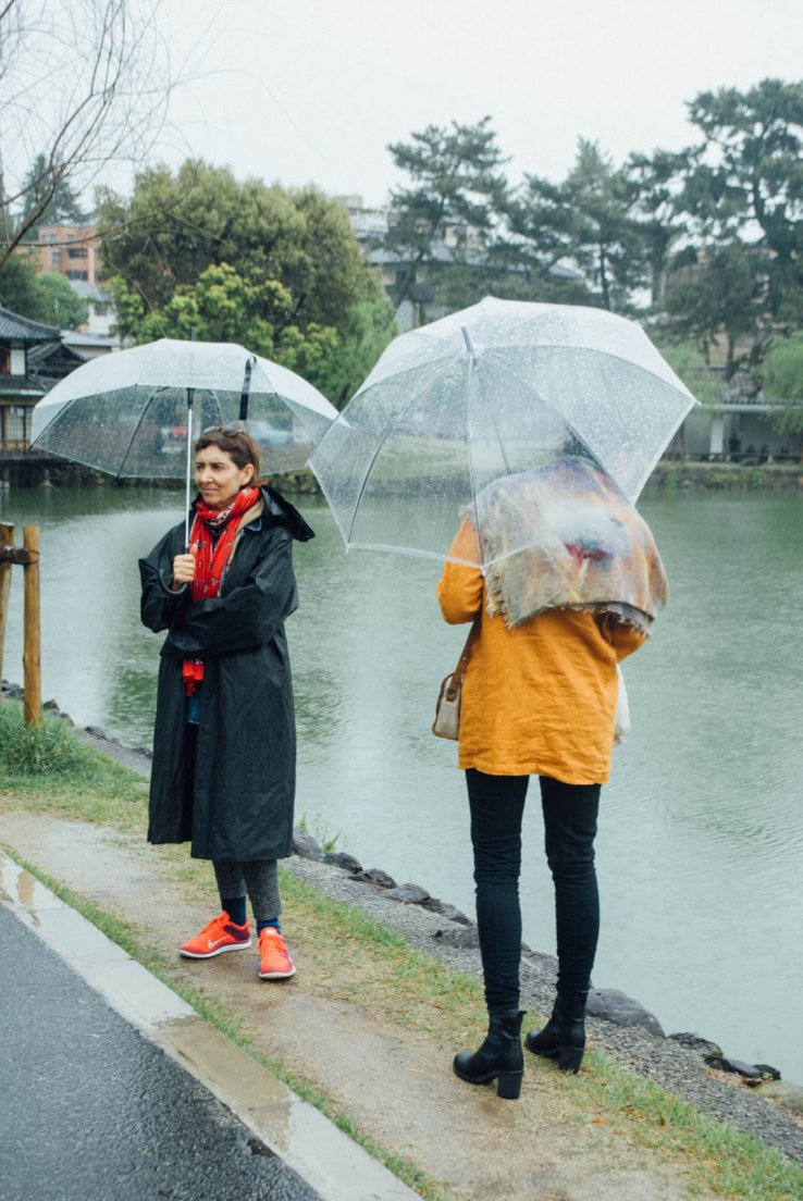 A mother and grown-up daughter standing by a pond holding typically japanese transparent umbrellas