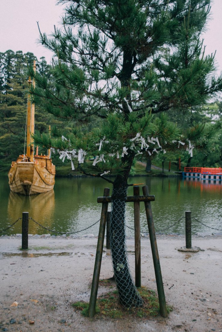 A tree covered in paper wishes in front of a small lake with a pretty barge floating there