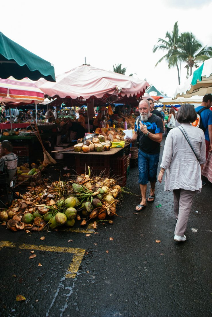 Tourists and locals passing by the coconut stall at a food market