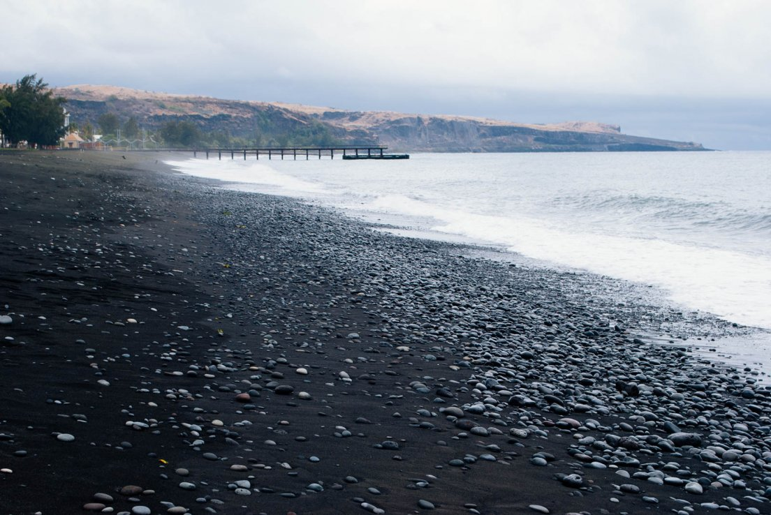 Black sand beach of Saint Paul with a pier lingering in the background by a stormy weather day