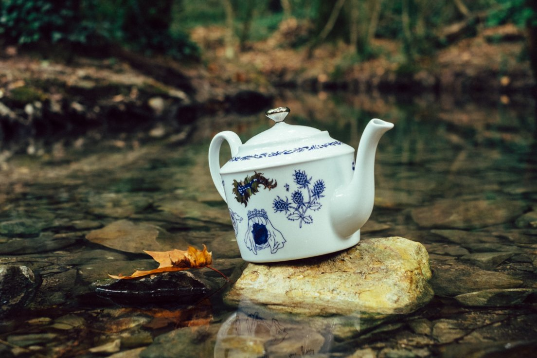 Blue teapot from Enchanteresse, a collection of hand-painted porcelains by messalyn, in the middle of a forest pond