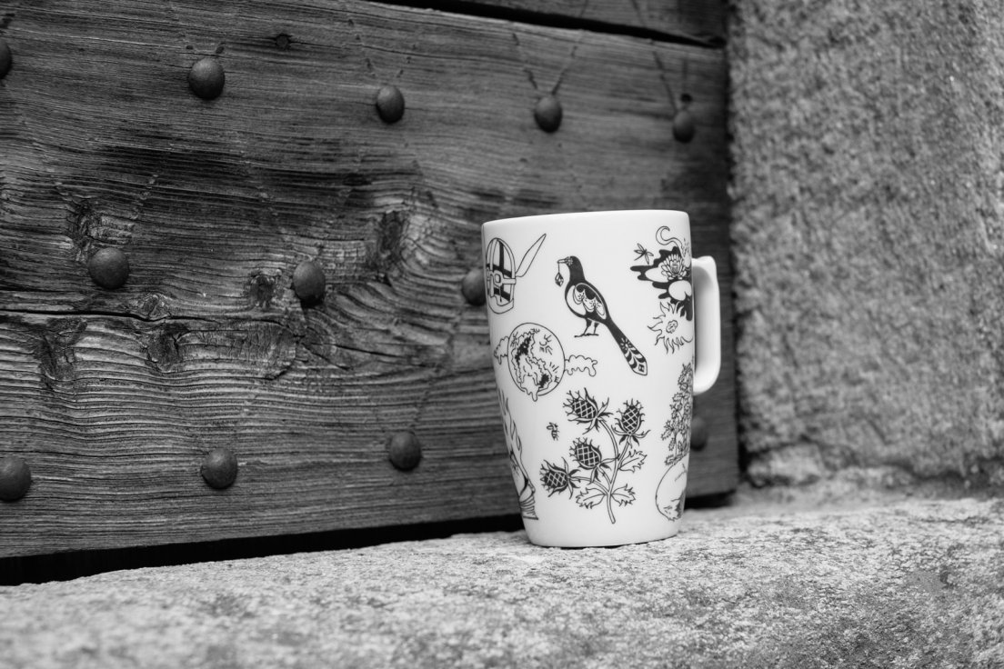 Black and white photograph of a mug from Enchanteresse, a collection of hand-painted porcelains by messalyn, in front of a medieval door