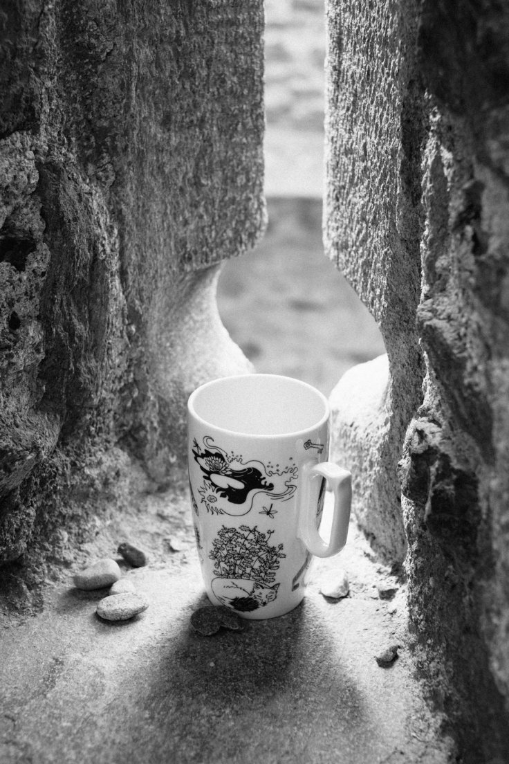 Black and white photograph of a mug from Enchanteresse, a collection of hand-painted porcelains by messalyn, on the windowsill of an arrowslit