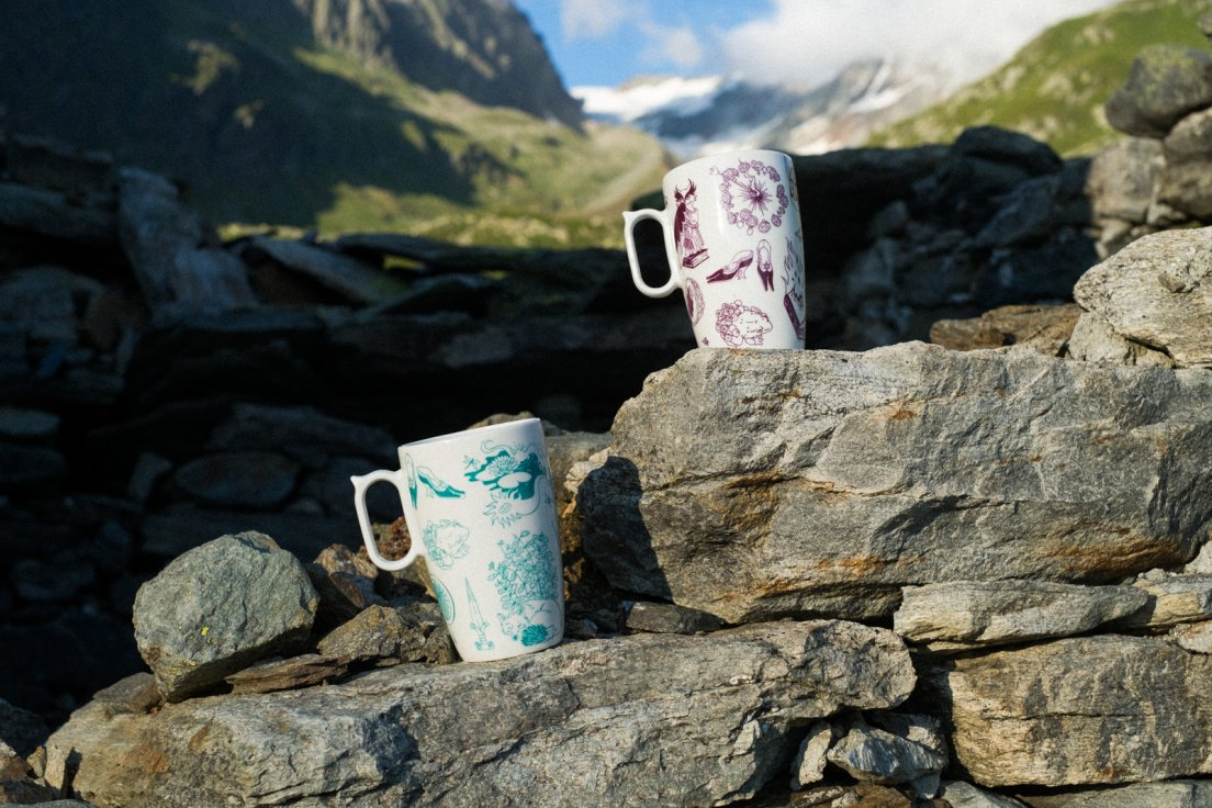 Purple and seafoam mugs from Enchanteresse, a hand-painted porcelain collection by messalyn, standing amongst the ruins of an abandoned village in the mountains