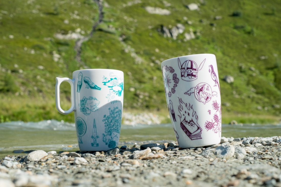 Purple and seafoam mugs from Enchanteresse, a hand-painted porcelain collection by messalyn, on the shoreline of a mountain torrent