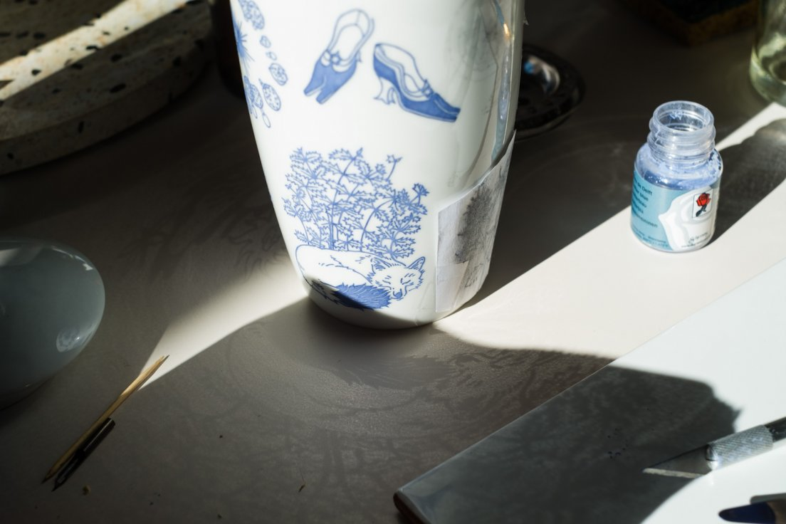 The drawings from the blue mug from Enchanteresse, a collection of hand-painted porcelains by messalyn, reflecting around on the table due to the morning sunlight