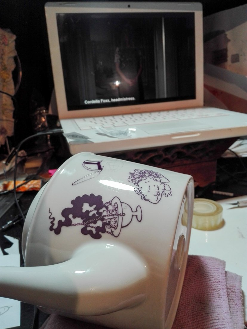 Work in progress of a purple teapot from Enchanteresse, a hand-painted porcelain collection by messalyn, in front of the tv show American Horror Story: Coven
