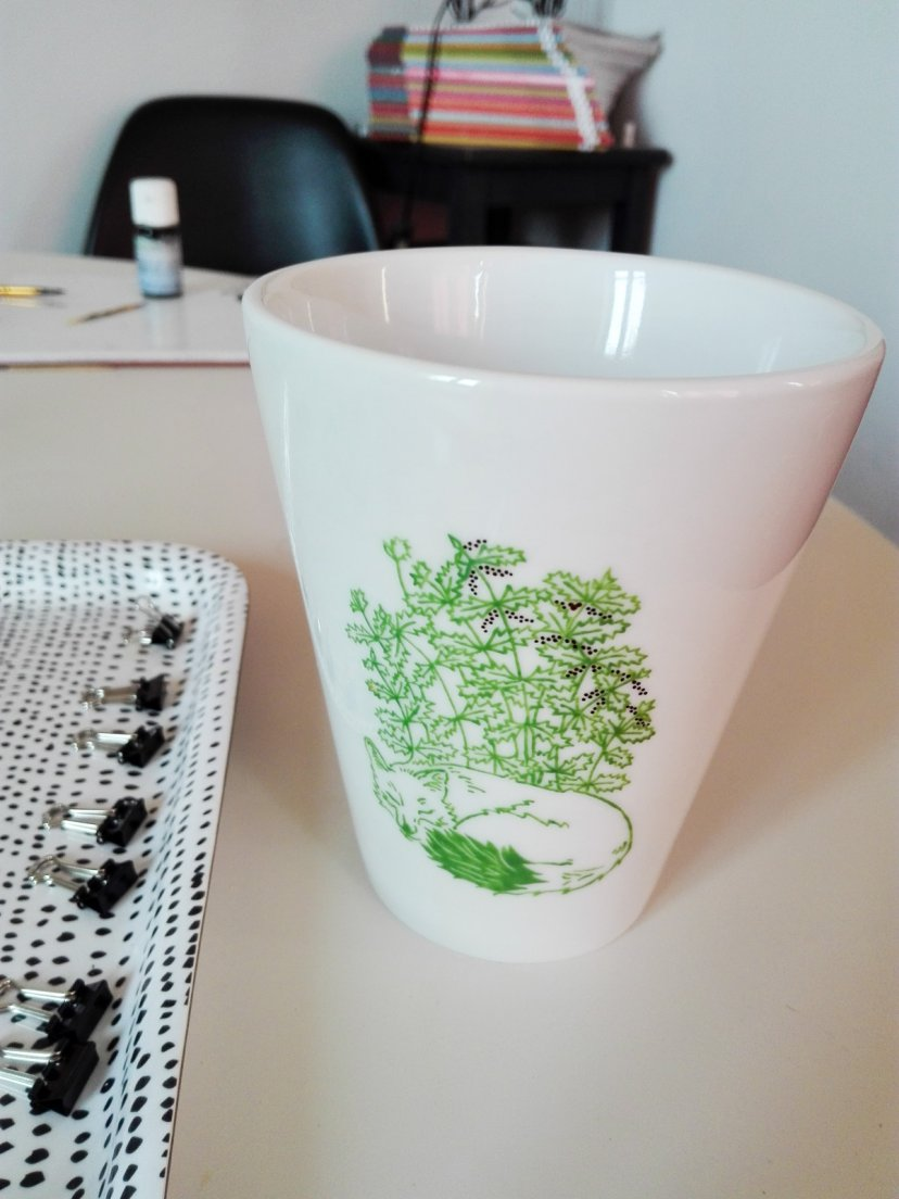 Painting in true matte gold the nettles seeds in the green Renard mug from Enchanteresse, a collection of hand-painted porcelains by messalyn