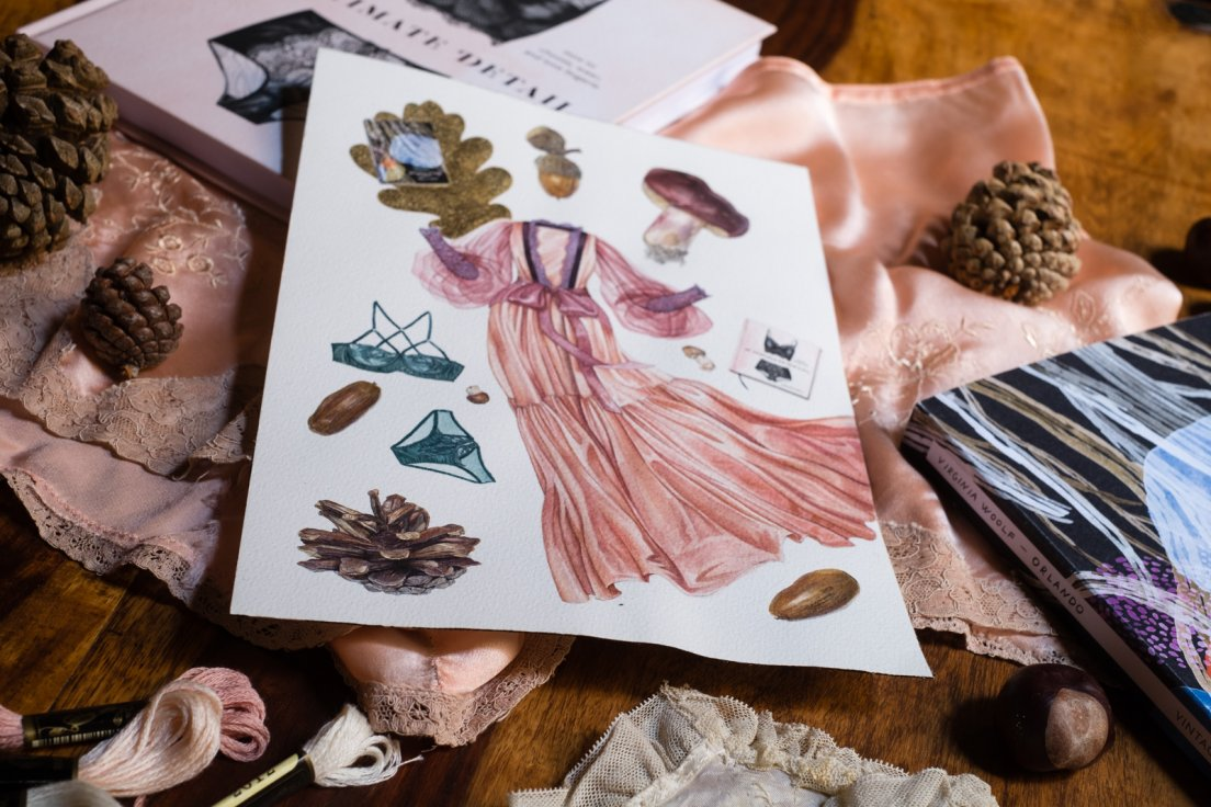 Photograph of an original watercolour featuring fashionable elements such as a green lingerie set, a lounging gown, Cora Harrington must-have book for lingerie lovers, Virginia Woolf's Orlando, but also realistic botanical depictions of mushrooms, acorns