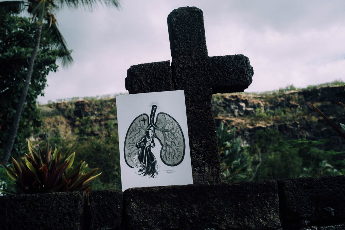 Reproduction print of a gothic illustration held up by a the cross of a grave, Reunion Island